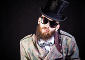 image of queer  - Stylish hipster in weird outfit before a black background - JPG