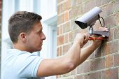 pic of security  - Security Consultant Fitting Security Camera To House Wall - JPG