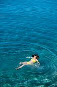 stock photo of top-hat  - Young woman in yellow swimsuit and big hat swimming and relaxing in the blue water sea - JPG