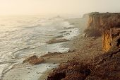 picture of landslide  - Sea coastal foggy sunset landscape of cliff edge with big cracks and withered plants after landslide - JPG
