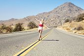 stock photo of arid  - Rear view of young woman with outstretched arms walking along yellow dividing line of empty road among arid landscape - JPG