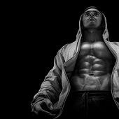 picture of physique  - Bottom view of young strong bodybuilder showing off his physique against black background - JPG