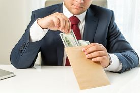 foto of politician  - Conceptual photo of bribed politician taking envelope with money - JPG