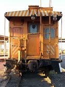 foto of caboose  - Yellow caboose on train on tracks in trainyard in ogden utah valley at base of rocky  - JPG