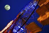 picture of amusement park rides  - View from under a moving big wheel of luna park with full moon