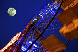 pic of amusement park rides  - View from under a moving big wheel of luna park with full moon  - JPG