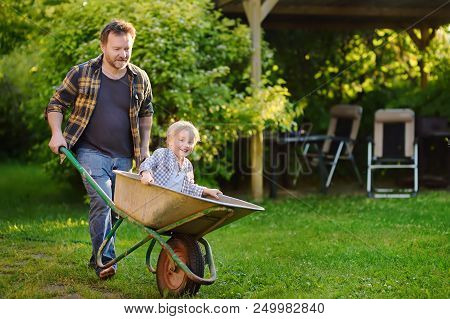 Happy Little Boy Having Fun In A Wheelbarrow Pushing By Dad In Domestic Garden On Warm Sunny Day Ac Poster