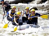 stock photo of raft  - Group of happy people with guide whitewater rafting and rowing on river - JPG