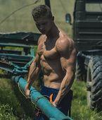 Bodybuilder Concept. Bodybuilder Man Pull Truck Trailer. Handsome Bodybuilder With Six Pack And Ab O poster