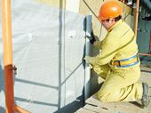 Facade Plasterer builder at outdoor external wall insulation with wind protection film