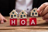 Businessperson Placing House Model Over Hoa Blocks poster