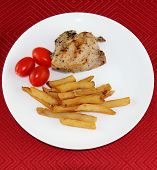 Chicken combo dish with fried potatoes and tomatoes