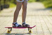 Girl Slim Legs In White Socks And Black Sandals Standing On Pavement On Plastic Pink Skateboard On B poster