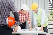 Engineer And Construction Team Wearing Safety Helmet And Looking Blueprint On The Table. They Are Wo poster