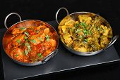 Indian chicken curry with saag aloo (spinach and potato) vegetable curry on traditional restaurant f