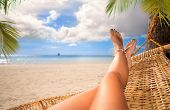 Sexy legs of a woman lying in a hammock on a beach by the open sea poster
