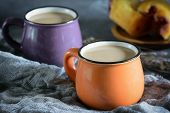 In A Small Orange Mug Coffee With Milk. Next A Purple Mug And A Cupcake In The Blur. Beautiful Still poster