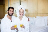 Happy young affectionate couple in bathrobes sitting in bedroom and having juice after bath poster