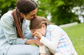 Young woman kissing her crying daughter on head, embracing and comforting her during chill in park poster