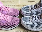 A Pair Of Pink Womens Sneakers And A Pair Of White Mens Sneakers On A Wooden Surface poster