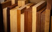 Thick wooden planks resting on a shelf. Mahogany, Alder, Ash, Bassswood, wood body planks used for e poster