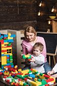 Mother Concept. Mother And Son Play Toy Bricks. Mother And Child Building Structure Model With Block poster