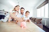 A Smiling Family Saves Money With A Piggy Bank. Happy Family At The Table In The Room. poster