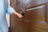 Girl Or Young Woman Puts Key In The Keyhole Of Garage Door Pvc poster