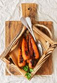 Baked Carrots In A Wooden Box With Parchment On A Beige Linen Tablecloth. The View From The Top,flat poster