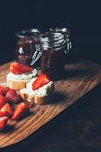 Selective Focus Of Fruit Jam In Different Jars, Sandwiches With Cream Cheese, Strawberry Slices And  poster