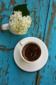 White Cup With Coffee With Composition Of White Hydrangea On Blue Wooden Background