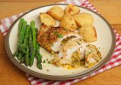 Chicken Kiev, stuffed with garlic and herb butter, served with potatoes and asparagus.