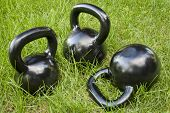 three heavy iron  kettlebells in green grass - outdoor fitness concept