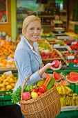 uma jovem mulher compra frutas e verduras em um mercado. alimentos frescos e saudáveis.