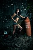 Dramatic night time portrait of a macho woman striking a stance with her hand resting on a propane gas bottle