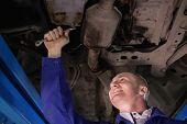 Smiling mechanic repairing the below of a car in a garage