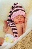 infant sleeping on a white sheepskin in a wicker basket.