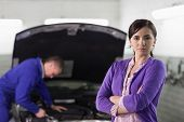 Woman looking at camera next to a car in a garage