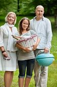 Portrait of a young female in casual wear holding picnic basket while standing with parents