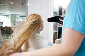 Hairdresser blow drying female customer's hair at parlor