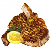 Grilled pork chops with sage and lemon, isolated on white background.