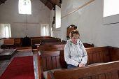 Una mujer sentada en un vacío iglesia orando