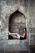 girl sit in stone decorative alcove on the fortress