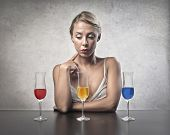 Beautiful young woman about to choose one of the three drinks standing in front of her