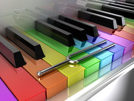 stock photo of rainbow piano  - Illustration of a silver tuning fork on a multicoloured piano - JPG
