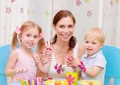 Happy young family playing with colorful paint at home, mother with two adorable children decorate Easter eggs