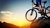 foto of riding-crop  - Young athlete standing on a rock with bicycle - JPG