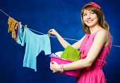 Young Housewife Hanging Clothes On Clothesline