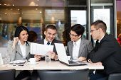 Group of four young business people gathered together at a table discussing an interesting idea in t
