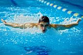 Swimmer in waterpool in action butterfly style